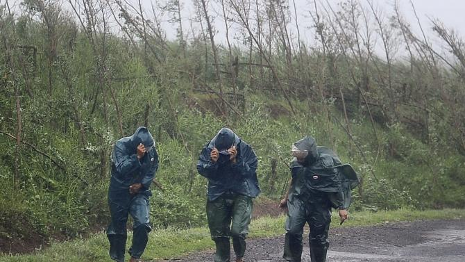 Residents cover their faces as they walk against strong wind and heavy rainfall under the influence of Typhoon Kalmaegi, in Xuwen county of Zhanjiang