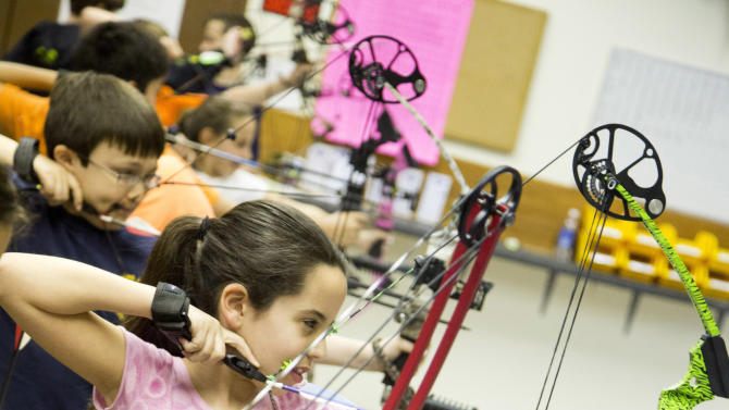 "In this April 13, 2012 photo, Nicole Alvira, of Fair Lawn, N.J., participates in the youth archery league at Targeteers Archery in Saddle Brook, N.J.  In schools and backyards, for their birthdays and out with their dads, kids are gaga for archery a month after the release of ""The Hunger Games."" Archery ranges around the country have enjoyed a steady uptick among kids of both sexes in the movie's lead-up, though 16-year-old heroine Katniss Everdeen, the archery ace seems to resonate with girls more than boys. (AP Photo/Charles Sykes)"