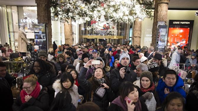 FILE - In this Thursday, Nov. 28, 2013, photo, a shopper takes a selfie as crowds pour into the Macy's Herald Square flagship store in New York. The government reports on sales at U.S. retailers in November on Thursday, Dec. 12, 2013. (AP Photo/John Minchillo)