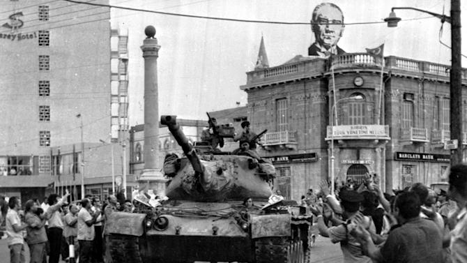 FILE- A Turkish army tank passes the Saray Hotel in the Turkish section of Nicosia, Cyprus, in this file photo dated July 24, 1974, as an image of Kemal Ataturk, founder of the modern Turkish republic looks down from a rooftop behind, as Turkey seized nearly 40 percent of the island and even more of its economic potential. After the 1974 invasion the people of Cyprus were forced to rebuild their lives and their economy from scratch, not something they Cypriot people ever wanted to to again, but following the 2013 collapse of the financial industry and the international financial bailout, even the most sanguine forecaster predicts many years of recession and sky-high unemployment. (AP Photo, File)