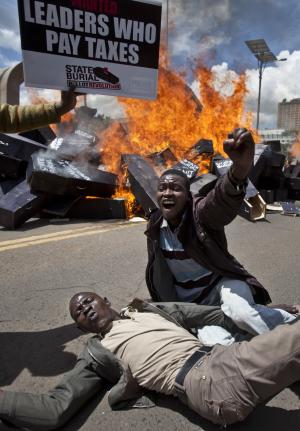 """Demonstrators celebrate after setting fire to mock coffins on which were written """"State Burial, Ballot Revolution"""" outside the Parliament in Nairobi, Kenya Wednesday, Jan. 16, 2013. Hundreds of demonstrators angered at outgoing Kenyan legislators, whose term ended earlier this week and who earn about $175,000 a year in a country where the average annual income is $1,700, doused 221 mock coffins with gasoline, one for each legislator, to protest against last week's attempt to award themselves a $110,000 bonus, which was vetoed by the president. (AP Photo/Ben Curtis)"""