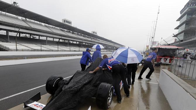 The crew of Takuma Sato, of Japan, pushes the car back to the garage area as rain halted track activity on the first day of qualifications for the Indianapolis 500 auto race at the Indianapolis Motor Speedway in Indianapolis, Saturday, May 18, 2013. (AP Photo/Darron Cummings)