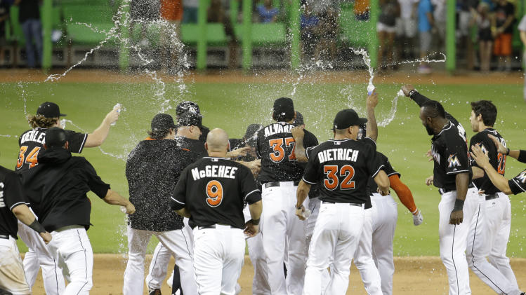 Miami Marlins players spray water onto Jeff Baker, not shown, after Baker drove in the winning run with a single to score Adeiny Hechavarria in the ninth inning during a baseball game against the Washington Nationals, Monday, July 28, 2014, in Miami. The Marlins defeated the Nationals 7-6. (AP Photo/Lynne Sladky)