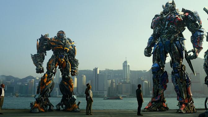 """This photo released by Paramount Pictures shows, from left, Hound, Bingbing Li as Su Yueming, Stanley Tucci as Joshua Joyce, Bumblebee, Jack Reynor as Shane Dyson, Nicola Peltz as Tessa Yeager, Mark Wahlberg as Cade Yeager, Optimus Prime, Drift, and Crosshairs, in a scene from the film, """"Transformers: Age of Extinction,"""" from Paramount Pictures. (AP Photo/Paramount Pictures, ILM)"""