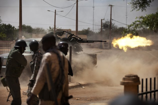 Malian soldiers fire a machine gun in Gao