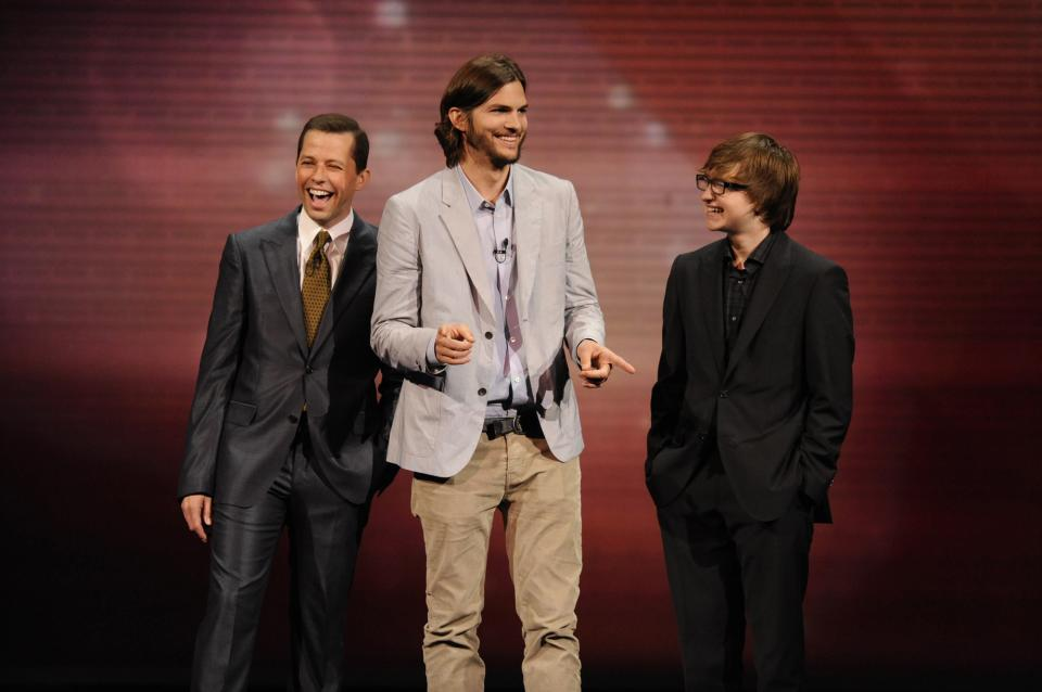 "FILE - In this May 18, 2011 file publicity image released by CBS, the cast of  ""Two and a Half Men,"" from left, Jon Cryer, Ashton Kutcher, and Angus T. Jones are shown during their presentation at CBS' Upfront at Carnegie Hall in New York. (AP Photo/CBS,  Jeffrey R. Staab)"
