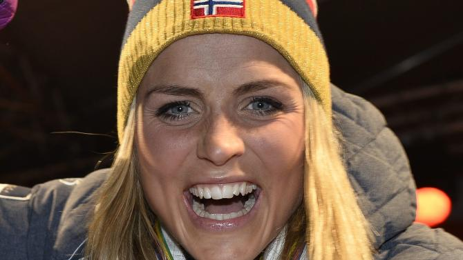 Johaug poses with her gold medals on the podium after the women's 30km mass start event at the FIS Nordic Skiing World Championships in Falun