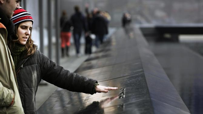 Tania Santos of Portugal reaches out to touch names engraved in memory of those who died in the terrorist bombing of the World Trade Center during a visit to the National September 11 Memorial and Museum, Monday, Feb. 25, 2013 in New York. Tuesday will mark the 20th anniversary of the terrorist bombing beneath the World Trade Center that killed six people in 1993. (AP Photo/Mark Lennihan)