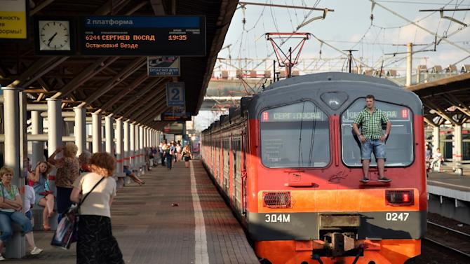 A man stands outside a local train end on July 25, 2014 near the Losinoostrovskaya station in a suburb of Moscow