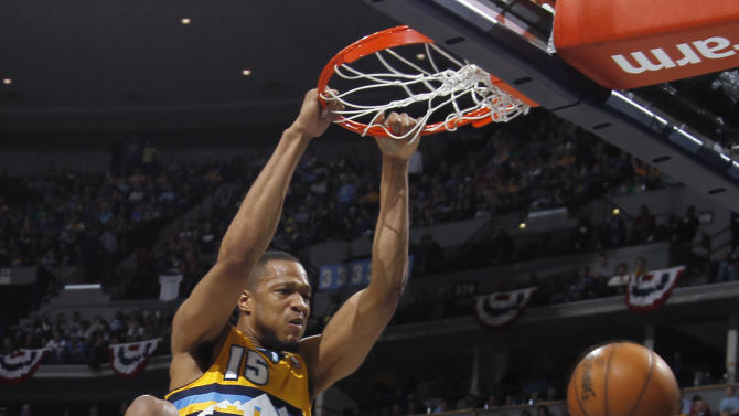 Denver Nuggets forward Anthony Randolph, front, hangs from the rim after dunking the ball for a basket as Golden State Warriors guard Klay Thompson, back left, and forward Harrison Barnes look on in the fourth quarter of the Warriors' 131-117 victory in Game 2 of the teams' NBA first-round playoff series in Denver on Tuesday, April 23, 2013. (AP Photo/David Zalubowski)