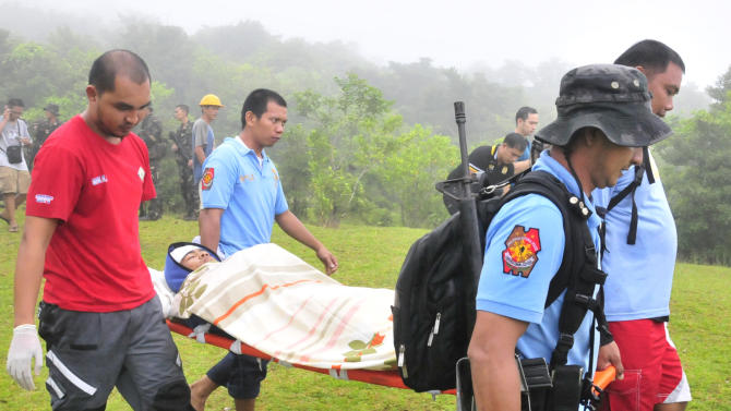 Police and rescuers carry Nicas Mabao Jr. to a waiting ambulance after surviving a steam-driven explosion of Mayon volcano, one of the Philippines' most active volcanoes, Tuesday, May 7, 2013 in Albay province about 450 kilometers (285 Miles) southeast of Manila, Philippines. Mayon volcano rumbled to life Tuesday, spewing room-sized rocks toward nearly 30 surprised climbers, killing five and injuring others that had to be fetched with rescue helicopters and rope. (AP Photo/Nelson Salting)