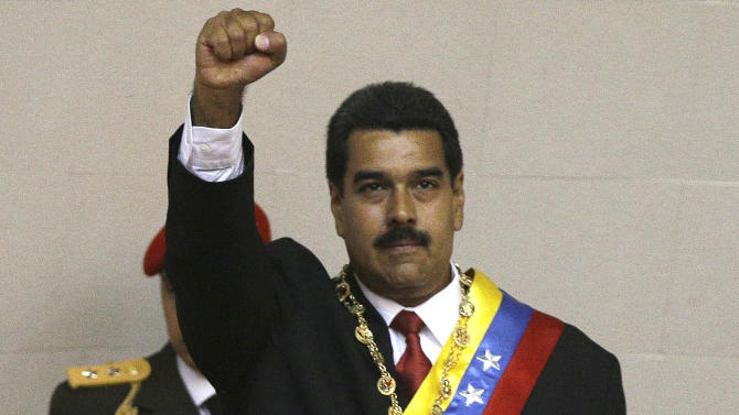Wearing the presidential sash, Venezuela's newly sworn-in President Nicolas Maduro raises his fist before delivering his inaugural speech at the National Assembly during his swearing-in ceremony in Caracas, Venezuela, Friday, April 19, 2013. (AP Photo/Fernando Llano)