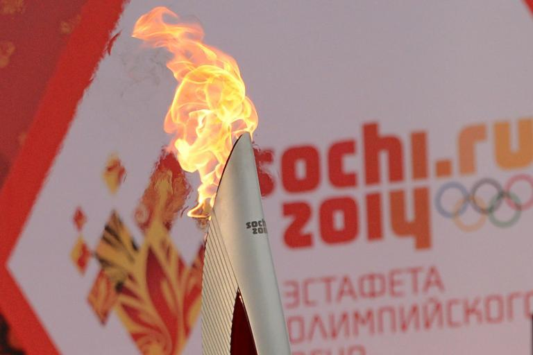 One of the Olympic torches rises in front of a poster with the Sochi 2014 Winter Olympic logo just outside the Red Square in Moscow, on October 7, 2013