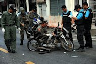 Members of a Thai bomb squad inspect the site of a motorcycle bomb blast triggered by suspected separatist militants in front of a market in the restive southern province of Narathiwat, on March 1, 2013. The blast wounded six people including a soldier, a day after Thailand signed its first known peace talk deal agreement with a rebel group in its Muslim-majority south