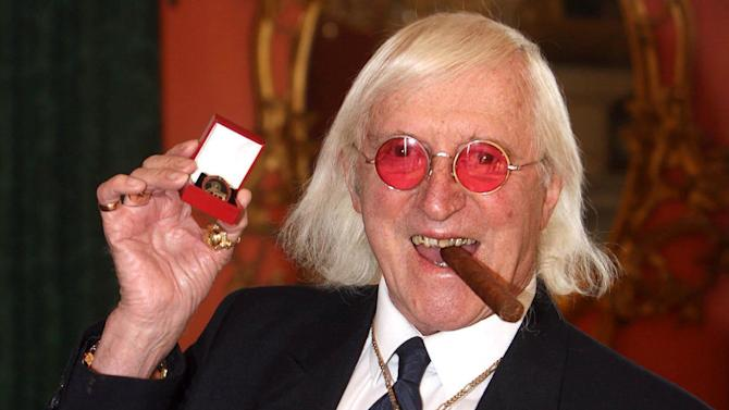 """FILE - This March 25, 2008 file photo shows Jimmy Savile holding a medal in London. At Savile's funeral in 2011, the priest delivering the homily was emphatic: the DJ and television host """"can face eternal life with confidence."""" But a year on, Savile's reputation is in ruins. Police have branded him one of Britain's worst sex offenders, accused of assaulting underage girls over half a century. Like those who feted and praised him on that November day, millions are wondering: How could he have duped so many for so long? (AP Photo/Lewis Whyld/PA Wire)"""