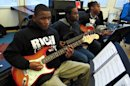 "In this March 22, 2013 photo, guitarists Kordae Maples, from left, Christian Nelson and Dallas Dodson rehearse a song at Stax Music Academy in Memphis, Tenn. The Stax Music Academy is an after-school program where teenagers from some of Memphis' poorest neighborhoods learn how to dance, sing and play instruments. The academy's students play annual shows in Memphis and have toured to Washington, Italy and Australia, helping spread the soulful ""Memphis Sound."" (AP Photos/Adrian Sainz)"