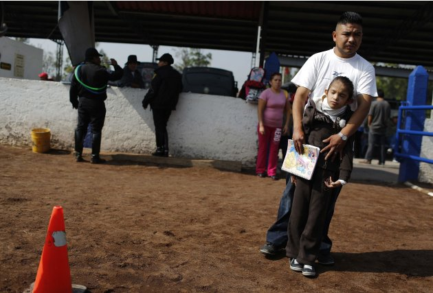 Man holds her daughter as they wait for a session of equine-assisted therapy at the Mounted Police Unit in Mexico City