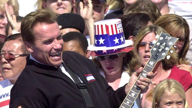 "FILE -- In this file photo taken Oct. 5, 2003,  Republican gubernatorial candidate Arnold Schwarzenegger, playfully strums a guitar to the  Twisted Sister song, ""We Ain't Going to Take it Anymore,"" during a campaign rally held at the Capitol in Sacramento, Calif.  Schwarzenegger, the former governor, who came to office during California's historic 2003 recall election, will  soon be releasing his autobiography, ""Total Recall: My Unbelievably True Life Story.""(AP Photo/Rich Pedroncelli, file)"