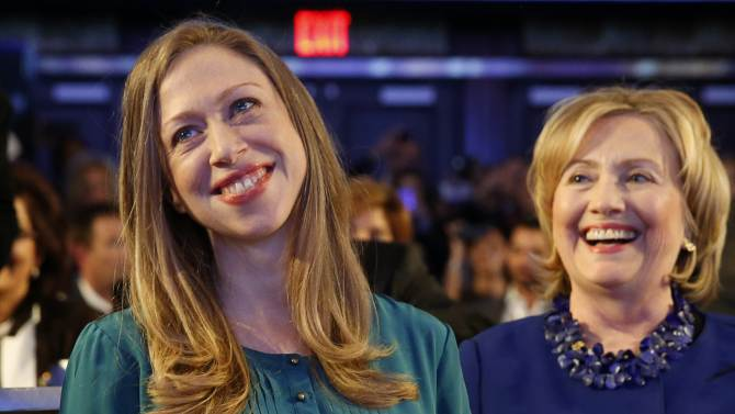 Former U.S. Secretary of State Hillary Clinton and her daughter Chelsea Clinton listen as U.S. President Barack Obama speaks at the Clinton Global Initiative in New York