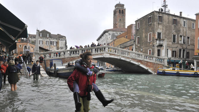 FILE - In this Nov. 1, 2012 file photo, people walk in high water near the Ponte delle Guglie in Venice, Italy, as high tides flooding the city force Venetians and tourists to don boots and navigate normally dry areas on wooden walkways. In 2012 many of the warnings scientists have made about global warming went from dry studies in scientific journals to real-life experience. (AP Photo/Luigi Costantini, File)