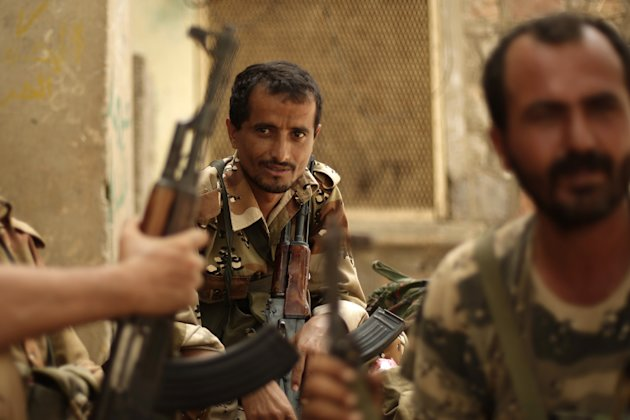 A Yemeni army soldier, center, looks on as he sits with his comrades at their post in the town of Jaar in southern Abyan province, Yemen, Friday, June 15, 2012. Yemen says government troops have kille