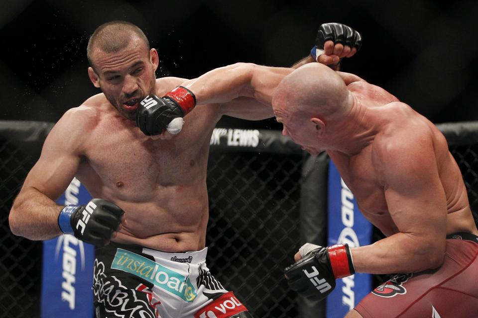 Ryan Jimmo's right hook connects to the face of Igor Pokrajac during during their light heavyweight bout at UFC 161 in Winnipeg on Saturday June 15, 2013. (AP Photo/The Canadian Press, John Woods)