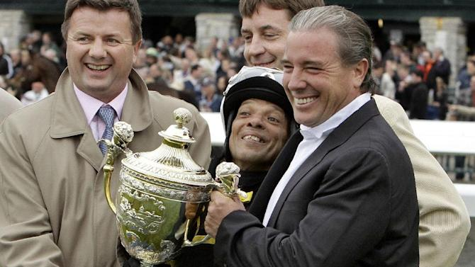 FILE - This is a Saturday, April 21, 2012 file photo horse race trainer Wesley Ward, right, holdong the Lexington Stakes horse race trophy as jockey Julio Garcia, centre, tries to see over it, after Ward's All Squared Away won the race at Keeneland race course in Lexington, Ky. American trainer Wesley Ward, is no stranger to success at the Royal Ascot, and will run six horses in Britain's iconic horse racing showcase as he tries to add to his three wins at the royal meeting. Royal Ascot begins on Tuesday June 17, 2014. (AP Photo/Garry Jones, File)