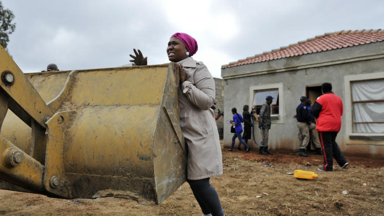 An unidentified woman unsuccessfully tries to prevent workers from demolishing her home in Lenasia, south of Johannesburg, South Africa, Friday, Nov. 9, 2012. South African police have supervised the demolition of some 44 homes since last week, saying they were constructed on illegally sold land. (AP Photo)