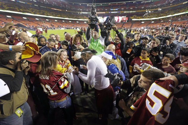 Washington Redskins quarterback Robert Griffin III signs autographs on the field during warmups before an NFL football game against the New York Giants in Landover, Md., Monday, Dec. 3, 2012. (AP Phot
