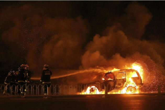 Firefighters try to extinguish fire on a vehicle after it burst into flames along a street in Beijing