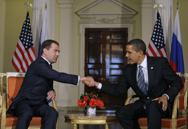 FILE - In this April 1, 2009, file photo U.S. President Barack Obama and Russian President Dmitry Medvedev, left, meet ahead of the G20 summit in London. Early in his presidency, Barack Obama replaced a George W. Bush-era plan for missile defense in Europe that had roiled relations with Russia. Obama says his four-stage plan would protect Europe and the United States as foes develop more sophisticated missiles. The announcement initially eased tensions with Moscow, which considered the previous plan a threat to its nuclear might. Obama has proposed cutting missile defense spending in 2013 by about 7 percent, to $9.7 billion. (AP Photo/Alexander Zemlianichenko, File)