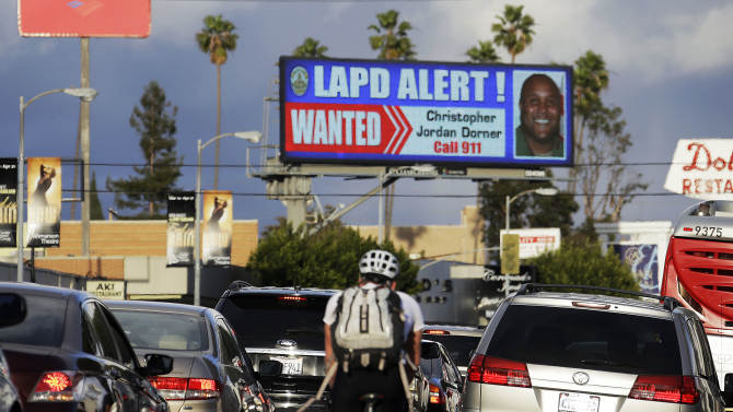 """In this Feb. 8, 2013 photo, commuters on Santa Monica Boulevard on the Westside of Los Angeles see a digital billboard displaying a large """"wanted"""" poster for former Los Angeles police Officer Christopher Dorner.  Dorner is suspected in a spree of violence as part of a vendetta against law enforcement after being fired by the department. He is also a suspect in the shooting deaths of a former LAPD captain's daughter and her fiance, and two other shootings that left an officer dead and two others wounded. Dorner's alleged killing spree hasn't just terrorized a large section of the country _ it has captured people's imagination and attention. (AP Photo/Reed Saxon)"""