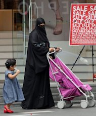 A woman walk with a child in front of a shopping mall in Kuala Lumpur. Malaysia, the number-one destination according to the findings, attracts Muslim visitors even during the ongoing fasting month of Ramadan