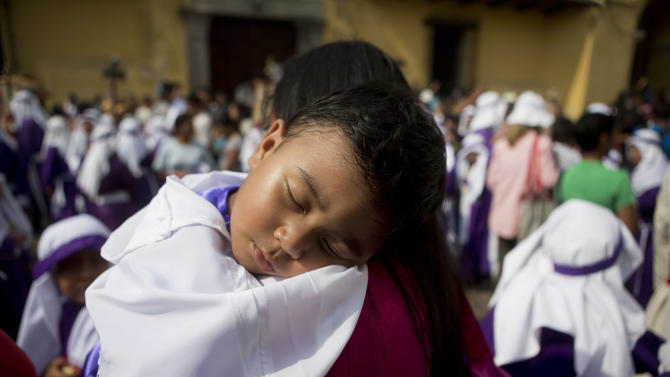A child rests on his mother's shoulder during a Holy Week procession in Antigua, Guatemala, Wednesday, April 1, 2015. La Merced church organized a procession for children who wanted to participate in the annual procession on Good Friday but where to small to do it. (AP Photo/Moises Castillo)