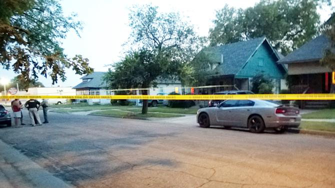 """In this Thursday, July 24, 2014 photo police tape surrounds a gray car outside a Wichita, Kan., where a 10-month-old girl died after being left inside a hot car. Authorities said Friday they have arrested the girl's foster parent on suspicion of aggravated endangerment but charges have not been filed. Police said the man had """"somehow forgotten"""" leaving the girl in the back seat after picking her up from the baby sitter late Thursday afternoon. (AP Photo/The Wichita Eagle, Matt Riedl)"""