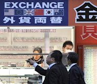 Pedestrians walk past a foreign currency exchange retail store in Tokyo. China and Japan started direct currency trading on Friday as Beijing marked another stage on its journey to foster the yuan&#39;s use internationally in line with its growing economic clout