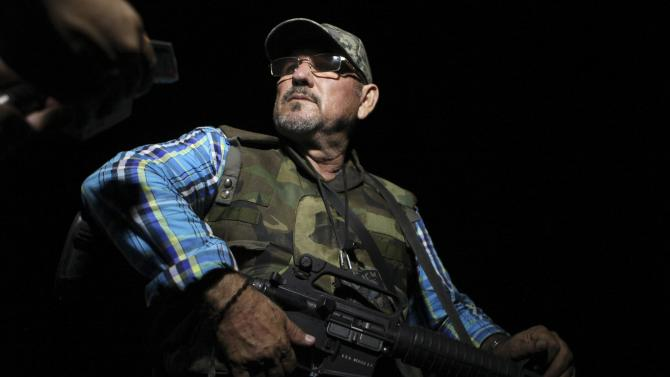 Vigilante leader Hipolito Mora stands guard after a shootout occurred in the town of La Ruana, Michoacan state