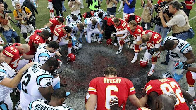Members of the Kansas City Chiefs and Carolina Panthers pray together following an NFL football game at Arrowhead Stadium in Kansas City, Mo., Sunday, Dec. 2, 2012. The Chiefs won 27-21. (AP Photo/Colin E. Braley)