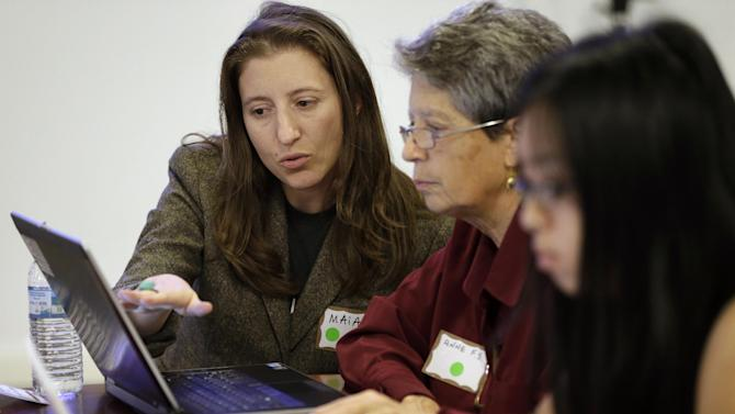 """In this Tuesday, Oct. 15, 2013 photo, Maia Weinstock, of Cambridge, Mass., left, a Brown University graduate, works with Anne Fausto-Sterling, of Cranston, R.I., center, a professor of biology and gender studies, during a Wikipedia """"edit-a-thon,"""" on the Brown campus, in Providence, R.I. They held the event, which brought together dozens of people, to train them on how to add and edit pages to Wikipedia, to coincide with Ada Lovelace Day, an annual observance started in Great Britain in 2009 to highlight women in technology and named for the English mathematician who died in 1852. (AP Photo/Steven Senne)"""