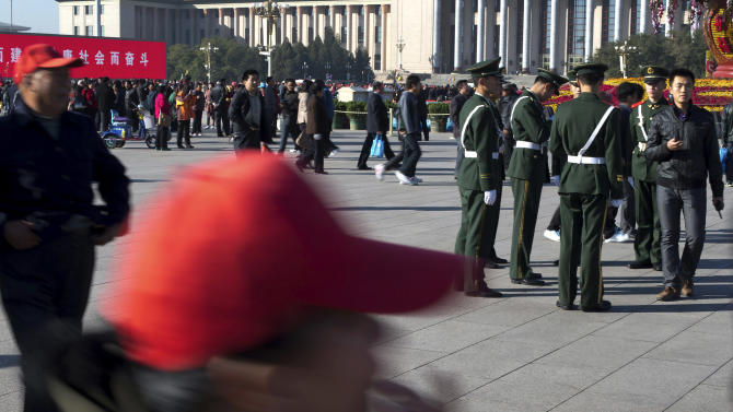 Visitors walk past as Chinese paramilitary policemen prepare for their duty at Tiananmen Square in Beijing Thursday, Nov. 1, 2012. Beijing is tightening security as its all-important Communist Party congress approaches, and some of the measures seem bizarre. Most of the security measures were implemented in time for Thursday's opening of a meeting of the Central Committee. (AP Photo/Andy Wong)