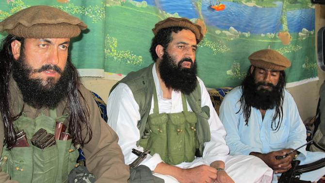 FILE - In this Saturday, Oct. 5, 2013 file photo, Pakistani Taliban spokesman Shahidullah Shahid, center, flanked by his bodyguards, talks to reporters at an undisclosed location in Pakistani tribal area of Waziristan along Afghanistan border. The Pakistani Taliban announced Saturday that the group will observe a one-month cease-fire as part of efforts to negotiate a peace deal with the government, throwing new life into a foundering peace process. Spokesman Shahidullah Shahid said in a statement emailed to reporters that the top leadership of the militant group has instructed all of its units to comply with the cease-fire. (AP Photo/Ishtiaq Mahsud, File)