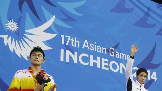 Gold medallist Hagino of Japan waves his hand next to silver medallist Sun of China after the men's 200m freestyle final swimming competition during the 17th Asian Games in Incheon