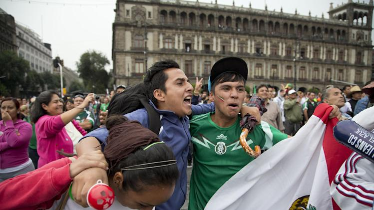 Mexico soccer fans celebrate a goal scored by their team against Croatia during a 2014 World Cup match in Mexico City's main square, the Zocalo, Monday, June 23, 2014. Mexico defeated Croatia, by 3-1, and will play the next phase of the world tournament. (AP Photo/Moises Castillo)