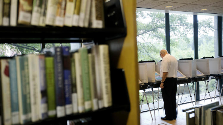 A voter casts his ballot at a polling site held in a public library, Tuesday, July 22, 2014, in Atlanta. Voters head to the polls on Tuesday to decide the U.S. Senate GOP runoff between Jack Kingston and David Perdue. The winner will face Democrat Michelle Nunn in November. In addition to the high-profile GOP U.S. Senate runoff, voters in Georgia on Tuesday will cast ballots in a number of other races, including four U.S. House runoffs and state school superintendent. (AP Photo)