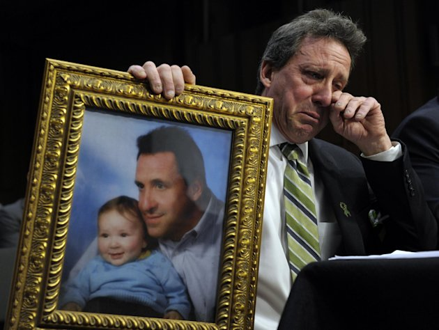 Neil Heslin, the father of a six-year-old boy who was slain in the Sandy Hook massacre in Newtown, Conn., on Dec. 14, holds a picture of himself with his son Jesse and wipes his eye while testifying o