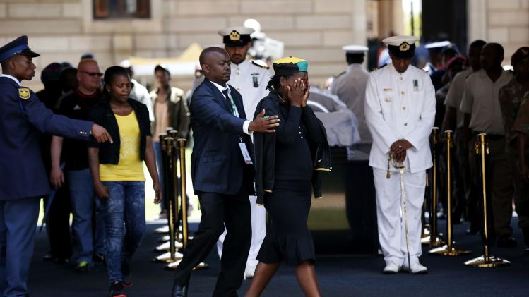 A woman reacts after paying her respects to former South African President Mandela in Pretoria