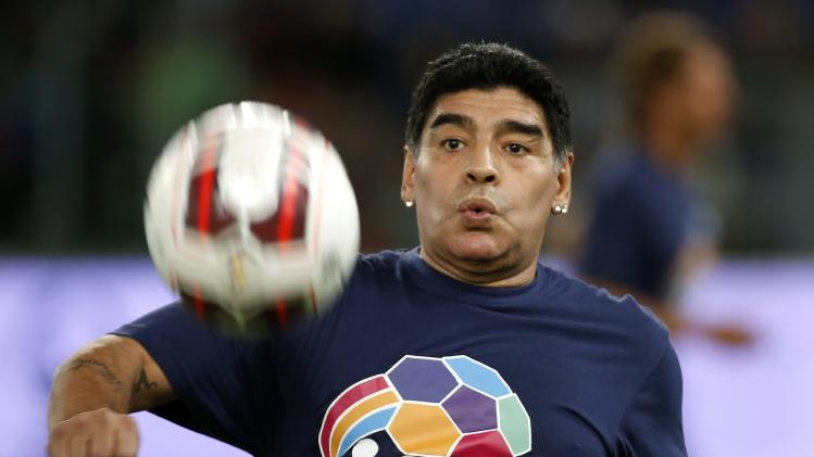 "Former soccer star Maradona warms up before the start of a special interreligious ""Match for Peace"" at the Olympic stadium in Rome"