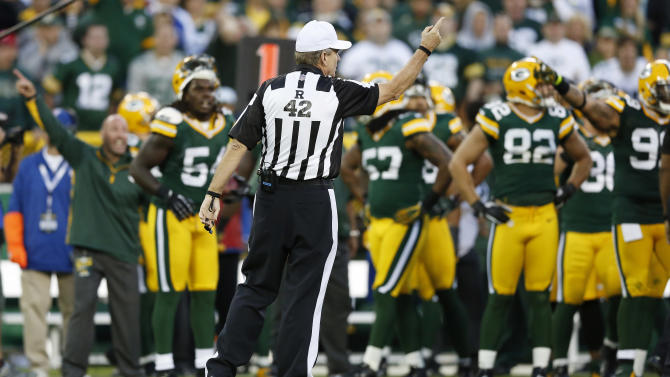 Referee Jeff Triplette signals New Orleans Saints' possession, after a video review, during the second half of the Saints' NFL football game against the Green Bay Packers on Sunday, Sept. 30, 2012, in Green Bay, Wis. Saints' Darren Sproles appeared to fumble a kickoff but officials ruled that he was down by contact. Replays showed that the ball clearly came out but the Packers were out of replay challenges, leaving Packers fans screaming at the officials for the second week in a row. (AP Photo/Tom Lynn)
