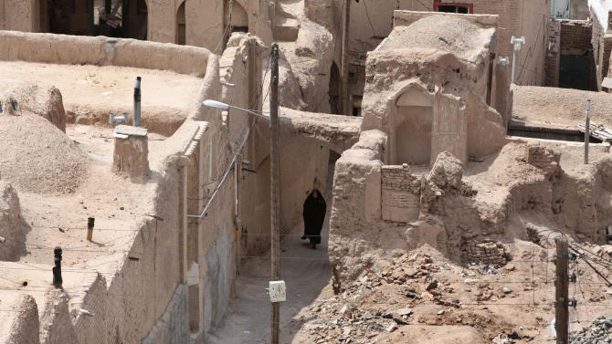 In this picture taken on Tuesday, May 6, 2013, an Iranian woman walks in an old district of the eastern city of Birjand, Iran. When struggling families in the eastern Iranian city of Birjand take measure of Mahmoud Ahmadinejad's presidency in its waning weeks, it's not about his browbeating oratory against the West or his battles with Iran's ruling clerics. Instead, it's the rows of simple two-story homes on the city's outskirts that sharply improved their lives. (AP Photo/Vahid Salemi)
