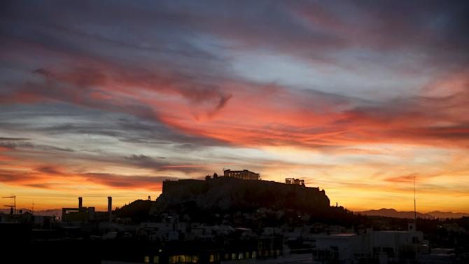 The ancient Parthenon temple atop the Acropolis hill is silhouetted against the sunset in Athens